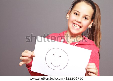 Happy attractive young girl with a lovely toothy smile holding a smiley drawn on a sheet of white paper, half body studio portrait on grey - stock photo