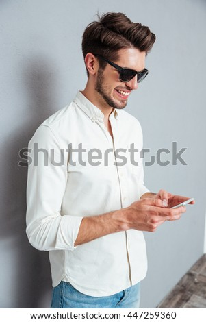 Happy attractive young man in sunglasses standing and using smartphone over grey background - stock photo
