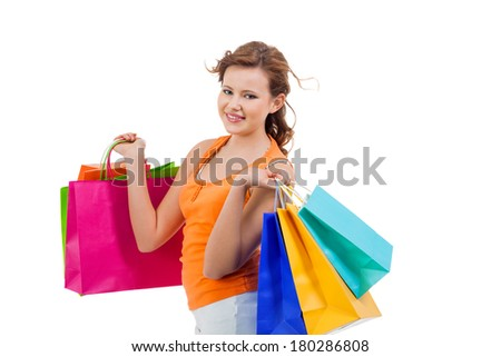 Happy attractive young shopaholic with her hands full of brightly coloured shopping bags from the seasonal sales standing smiling at the camera, isolated on white
