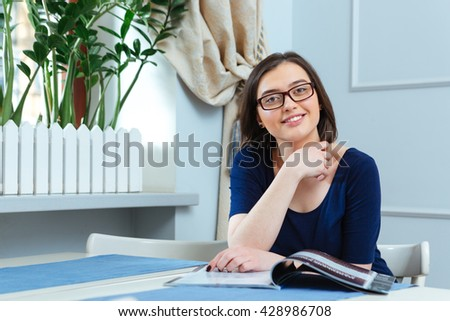 Happy attractive young woman in glasses reading magazine in cafe - stock photo
