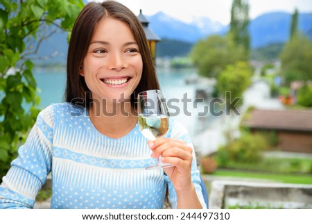 Happy attractive young woman smiling in pleasure as she sits outdoors and raises her glass of champagne in a celebratory toast - stock photo