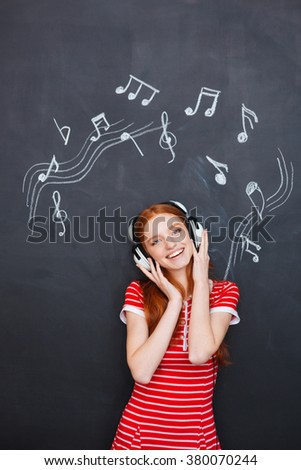 Happy attractive young woman standing and listening to music in headphones over blackboard background - stock photo