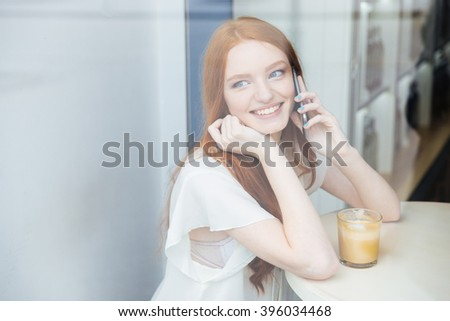 Happy attractive young woman talking on mobile phone and drinking coffee in cafe  - stock photo