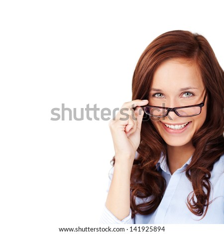 Happy attractive young woman with a lovely smile peering over her glasses at the camera, isolated on white with copyspace - stock photo