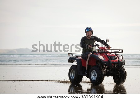 Happy ATV driver on the Ninety Mile Beach, New Zealand