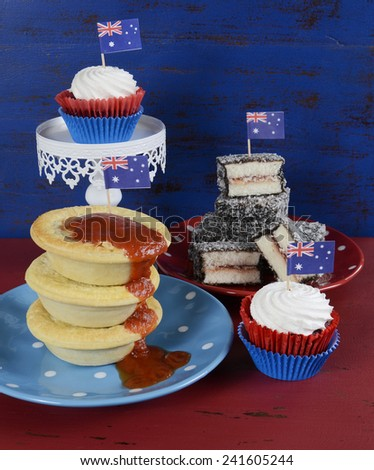 Happy Australia Day January 26 party food with iconic meat pies, lamingtons and cupcakes on dark red and blue vintage rustic recycled wood background. - stock photo