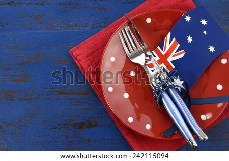 Happy Australia Day, January 26, theme table setting with red polka dot plate and Australian flag decoration on dark blue wood background. - stock photo