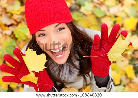 Happy autumn woman playing in leaves. utumn portrait of happy lovely and beautiful mixed race Asian Caucasian young woman in forest in fall colors.