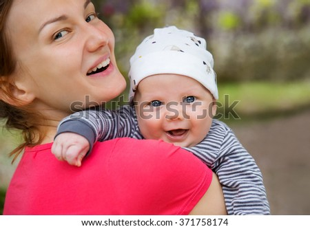 Happy baby and mother on nature in the park - stock photo