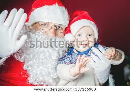 Happy baby and Santa Claus say hello and wave hand! Child dressed in red Santa hat. Xmas and New Year holiday!