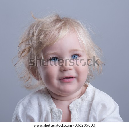 happy baby blue eyes blonde long hair gray background - stock photo