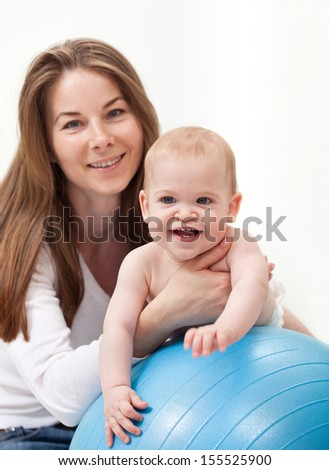 Happy baby boy and his mother playing with large ball - stock photo