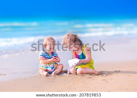 Happy baby boy and little curly toddler girl, brother and sister, playing with a huge sea shell in sand on a beautiful exotic tropical beach with turquoise water having fun on vacation