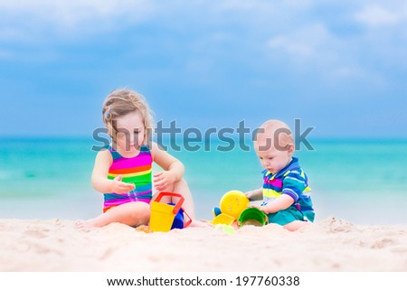 Happy baby boy and little curly toddler girl, brother and sister, playing with toy buckets and plastic shovel digging in sand on a beautiful exotic tropical beach with turquoise water  - stock photo
