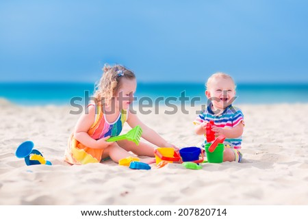 Happy baby boy and little curly toddler girl, brother and sister, playing with toy buckets and plastic shovel digging in sand on a beautiful exotic tropical beach with turquoise water