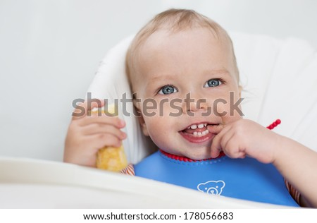 happy baby boy eating bread crackers and dabbles on white background
