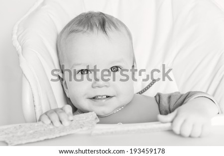 happy baby boy eating bread crackers and dabbles on white background ( black and white )