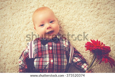 happy baby boy gentleman with a flower Gerbera - stock photo