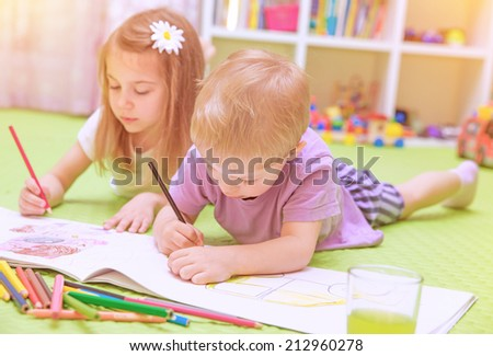 Happy baby boy & girl enjoying homework, preschool developing drawing skills, talented children learning art, kids back to school concept - stock photo