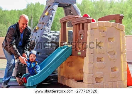 Happy baby boy has slid on the chute and his father has caught him - stock photo
