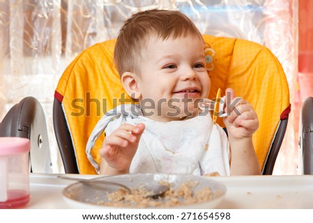 Happy baby boy holding pacifier and smiles at breakfast - stock photo