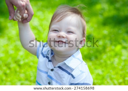 Happy baby boy learning to run walk in park holds hand - stock photo