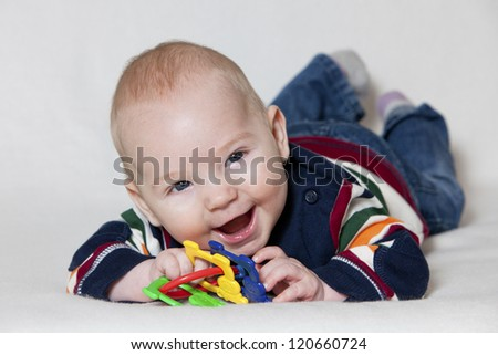 Happy baby boy lying on his stomach and playing with toy and smiling. - stock photo