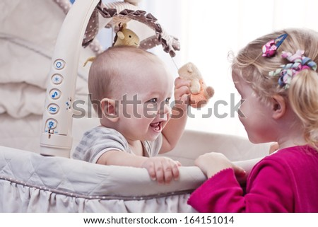 Happy baby boy playing with his sister sitting in the cradle - stock photo