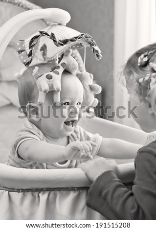 Happy baby boy playing with his sister sitting in the cradle ( black and white ) - stock photo