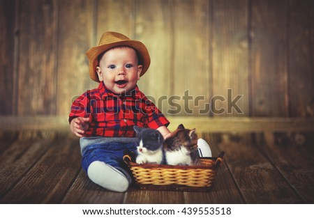 happy baby boy playing with kittens on a wooden background - stock photo
