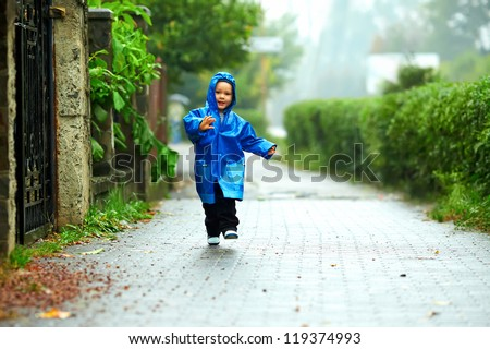 happy baby boy running the street under the rain