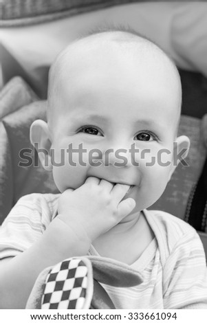 happy baby boy sitting in a blue stroller for a walk  ( black and white ) - stock photo