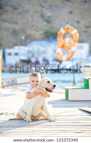 Happy baby boy with him dog on berth in summer - stock photo