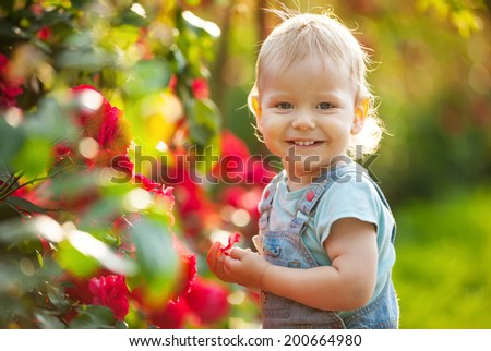 Happy baby boy with red roses in summer garden  - stock photo