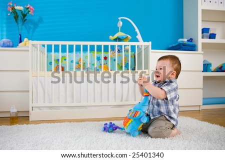 Happy baby boy ( 1 year old ) sitting on floor at home and playing with soft toys at children's room, smiling. - stock photo