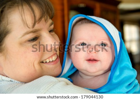 Happy baby bundled up in towel after bath being held by mother - stock photo
