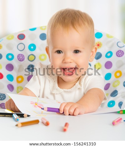 happy baby child draws with colored pencils crayons - stock photo
