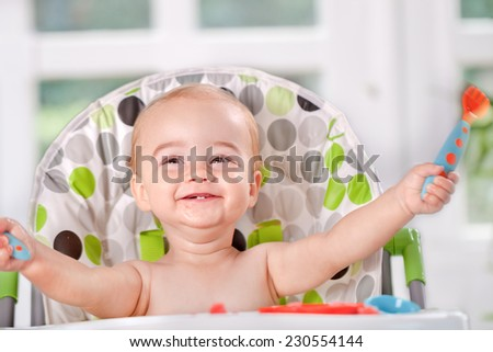 Happy baby child eats itself with a spoon and fork - stock photo