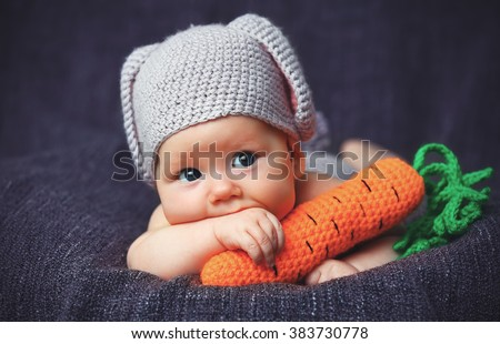 happy baby child in costume a rabbit bunny with carrot on a grey background - stock photo