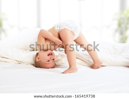 happy baby child play fun in bed - stock photo