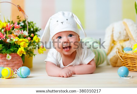 happy baby child with Easter bunny ears and colorful eggs and flowers