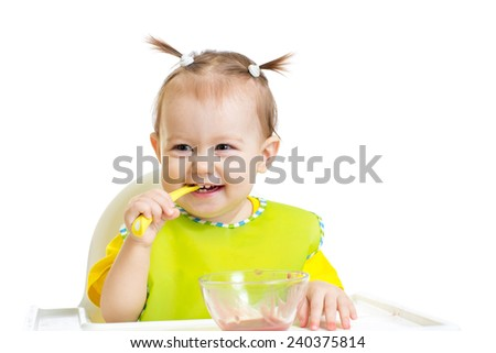 Happy baby eating with spoon sitting at table
