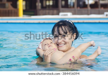 Happy baby girl enjoying her first swim in the pool. Mother and daughter on summer vacation. Family values. Parenting and child entertainment.  Mom in the decree