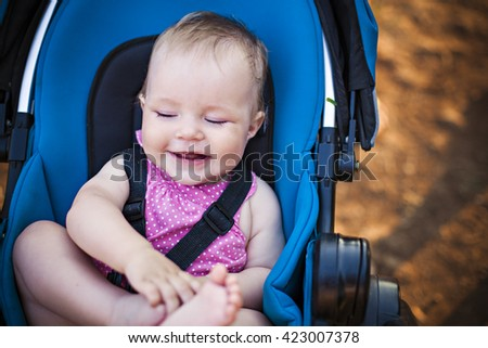 Happy baby girl in a stroller. Sitting and holding her little foot, looking on the side. - stock photo