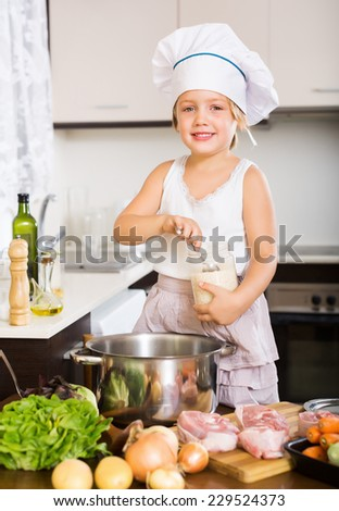 Happy baby girl in cook hat cooking soup  with ladle at home