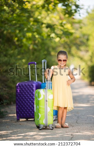 happy baby girl is going on a trip, pack a suitcase. happy little girl playing with a little retro suitcases outdoor. Child with airline tickets