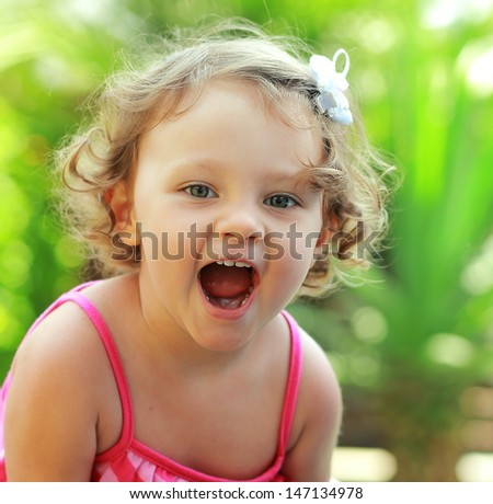 Happy baby girl joy with opened mouth outdoor summer background. Closeup - stock photo