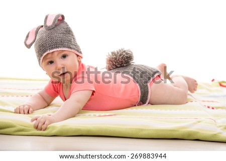 Happy baby girl laying on blanket and wearing knitted bunny costume - stock photo