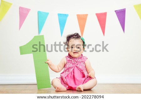 Happy baby girl on her first birthday party seated on the floor
