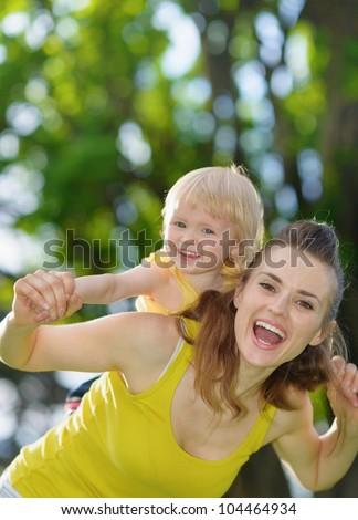 Happy baby girl piggybacking mother - stock photo